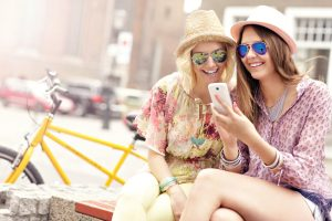 Two women enjoying a shared text. Avoid texting anythjng inflammatory or abusive, or even startlingly good news.
