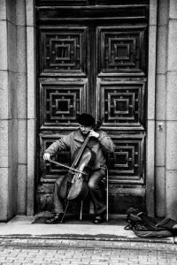 b&w photograph of a man playing his cello busking in  the doorway of what is probably a cathedral.  The doos is wooden and elaborately carved. He is playing with deep concentration and love of his music. What is the one loving, dedicated thing that you can do for your relationship today? Now.