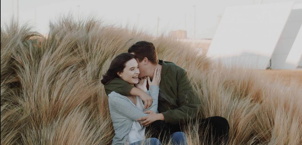 A hapy couple in a field of waving grass. They are happy in this moment, but a happy ending depends on when they stop the story.