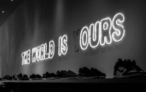 "LED sign showing ""The world is (y)ours"" illustrates the connection between yours, mine and ours which inevitably comes up in money-talk."